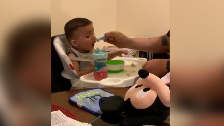 Dad feeding baby who is looking at a stuffed toy on the table