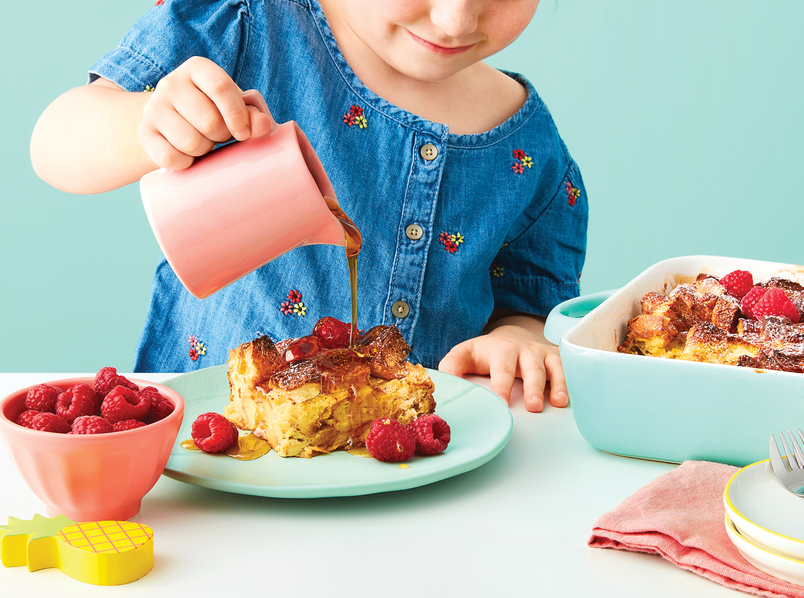 child pouring syrup on French toast