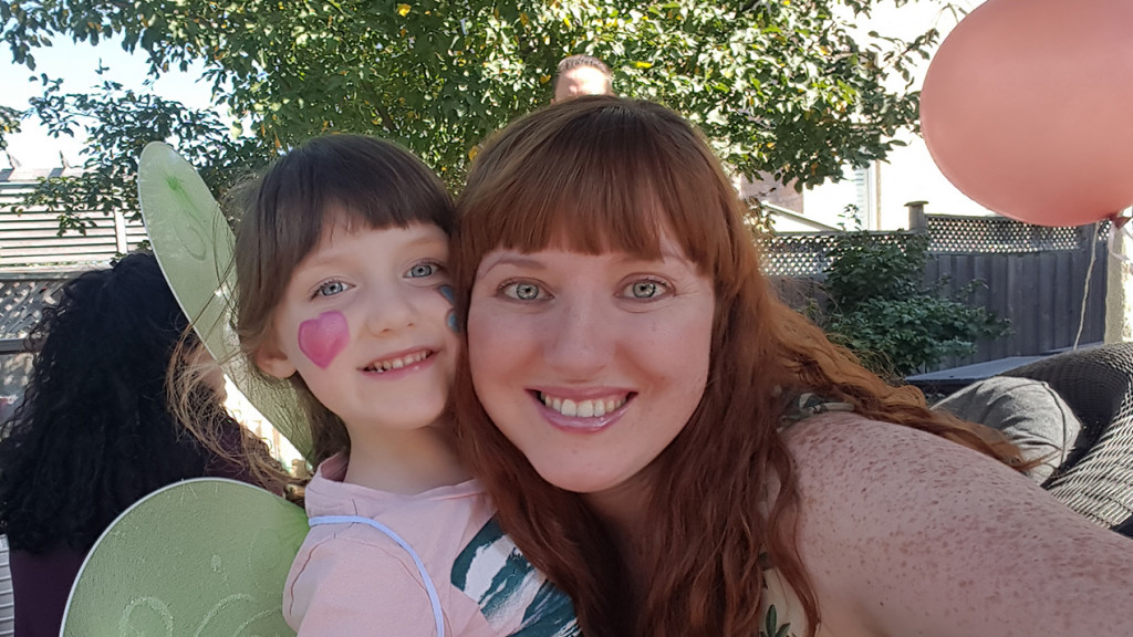 Mother and daughter smile with face paint