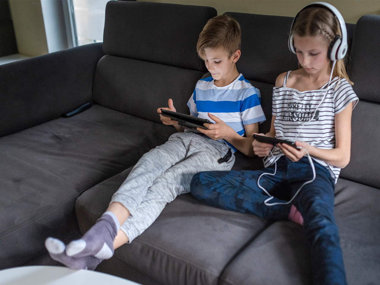 boy and girl watch screens on the couch