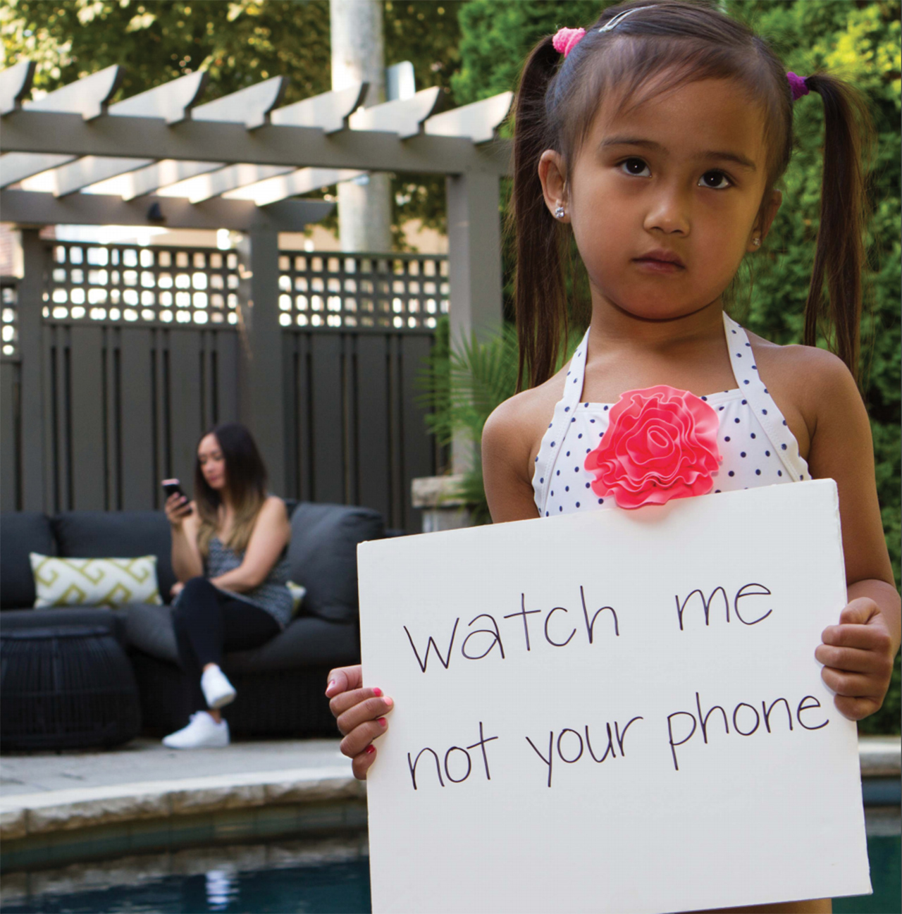 little girl in a bathing suit holding a sign that says 'watch me not your phone' while her mom looks at her phone in the background