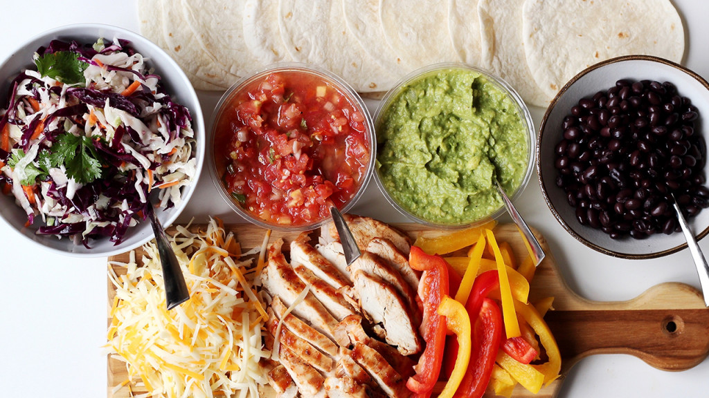 Fajita fixings like chicken, cheese, guac, salsa and tortillas on a platter