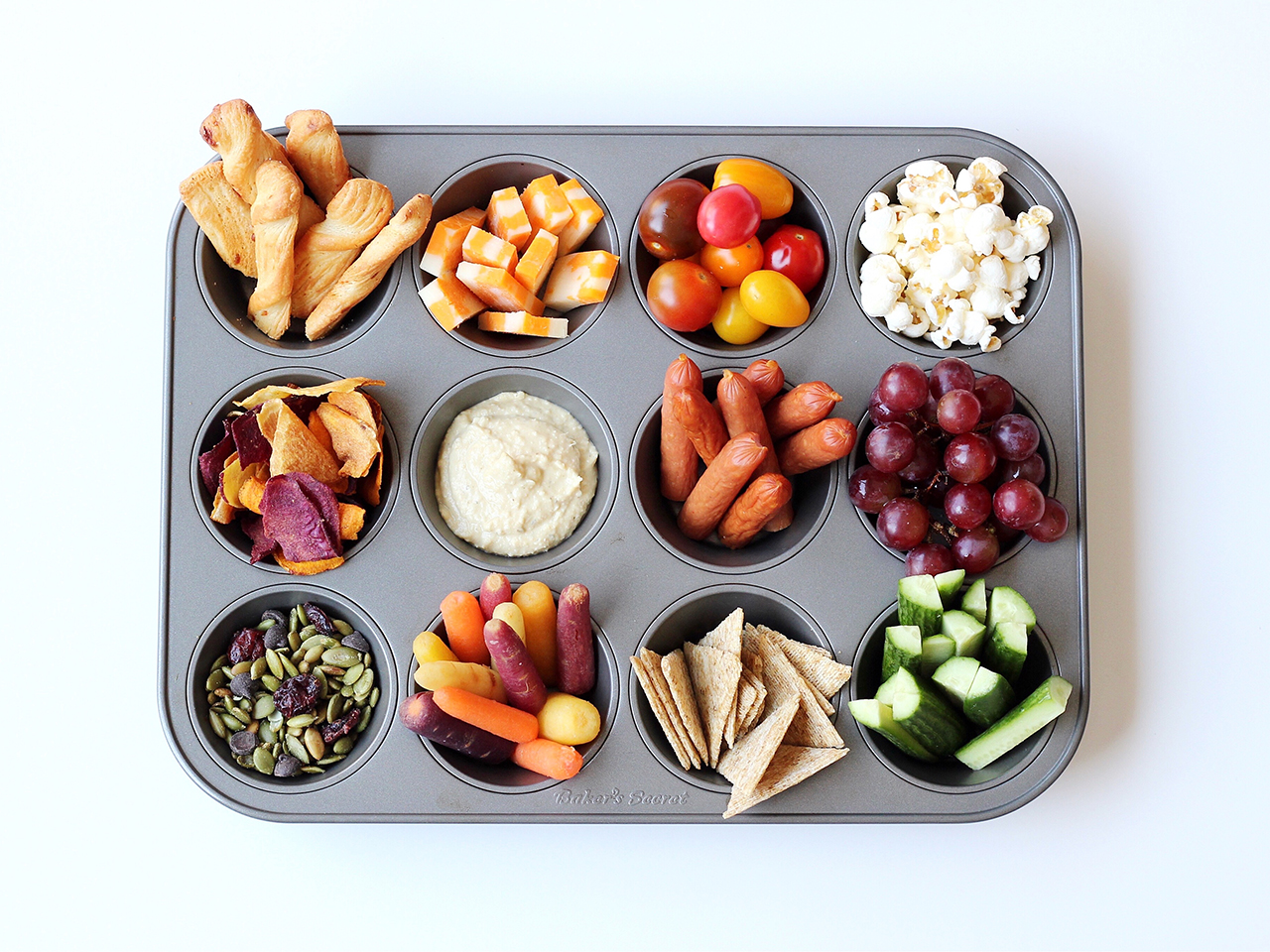 muffin tray filled with different snacks