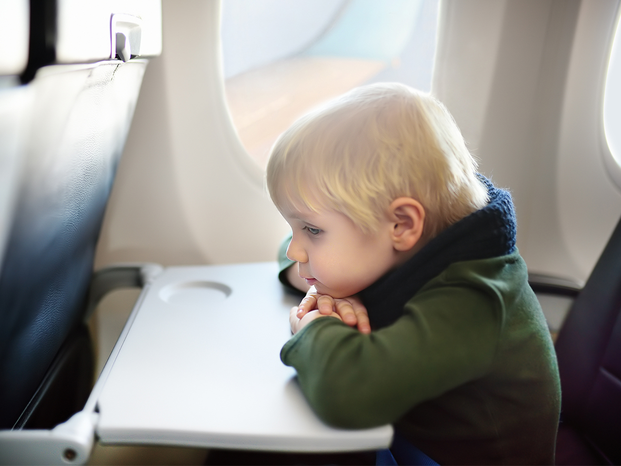 Lonely young boy sitting on airplane