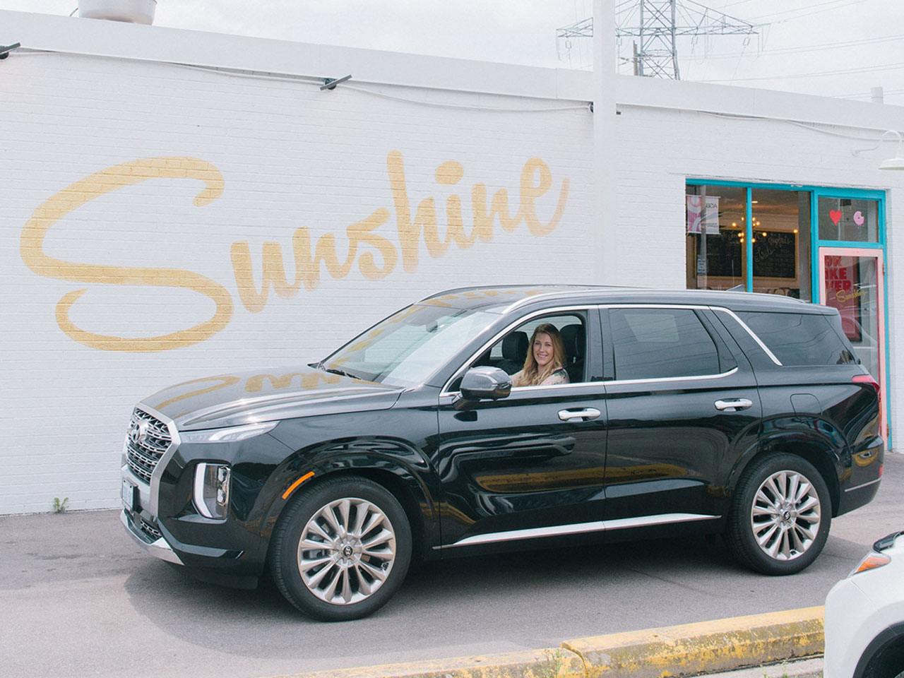 """Renee in Hyundai Palisade outside a building that says """"sunshine"""" on the wall"""