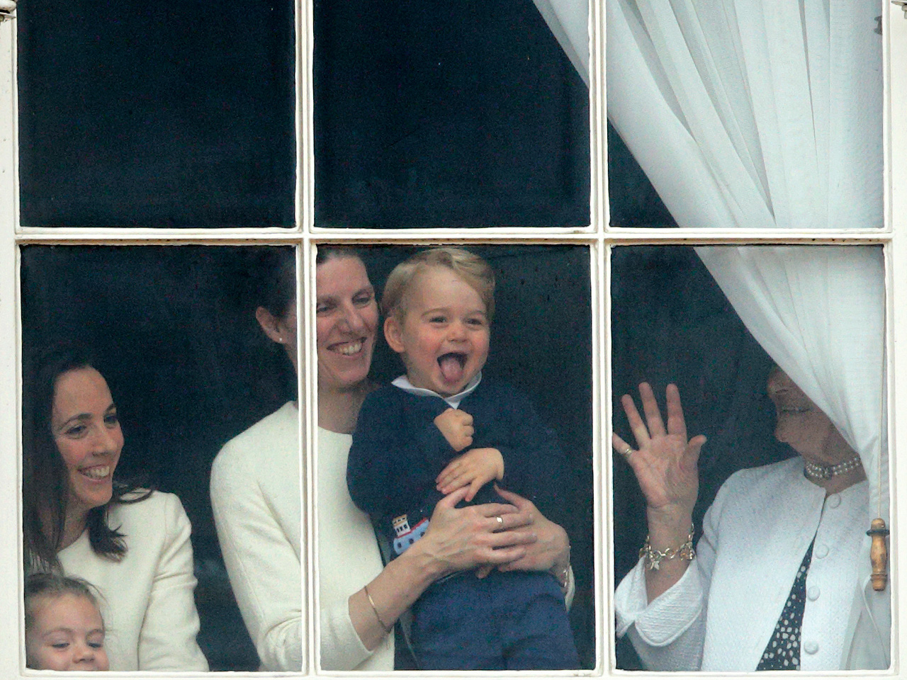 prince george and his nanny maria in the window of buckingham palace sticking out his tongue