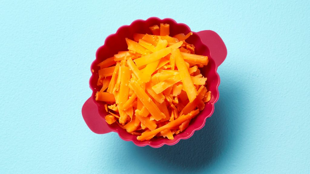Shredded cheddar cheese in a pink cup