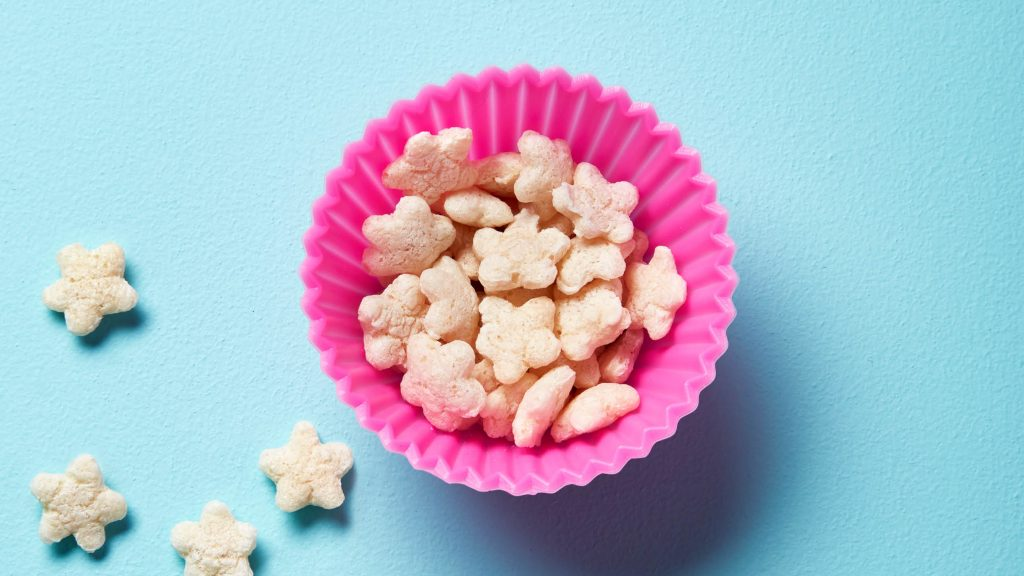 a pink bowl of baby puff snacks