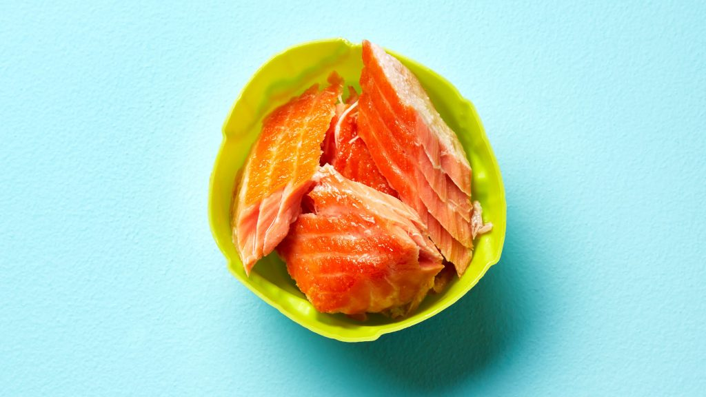 Chunks of cooked salmon in a green cup