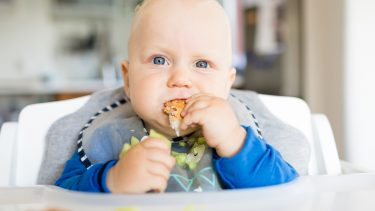 baby eating a piece of bread and some avocado