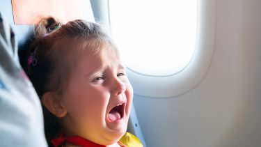 a little girl crying on an airplane