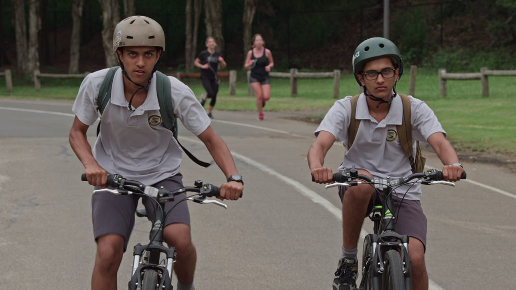Two teen boys in uniforms riding bicycles
