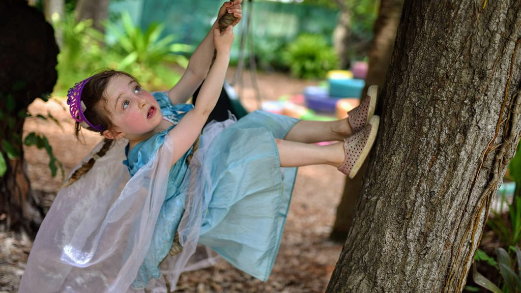 young girl in fairy costume climbing tree