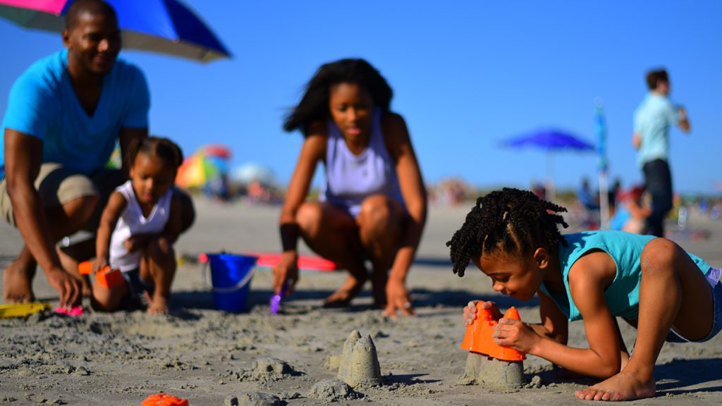 family playing in the sand on the beach