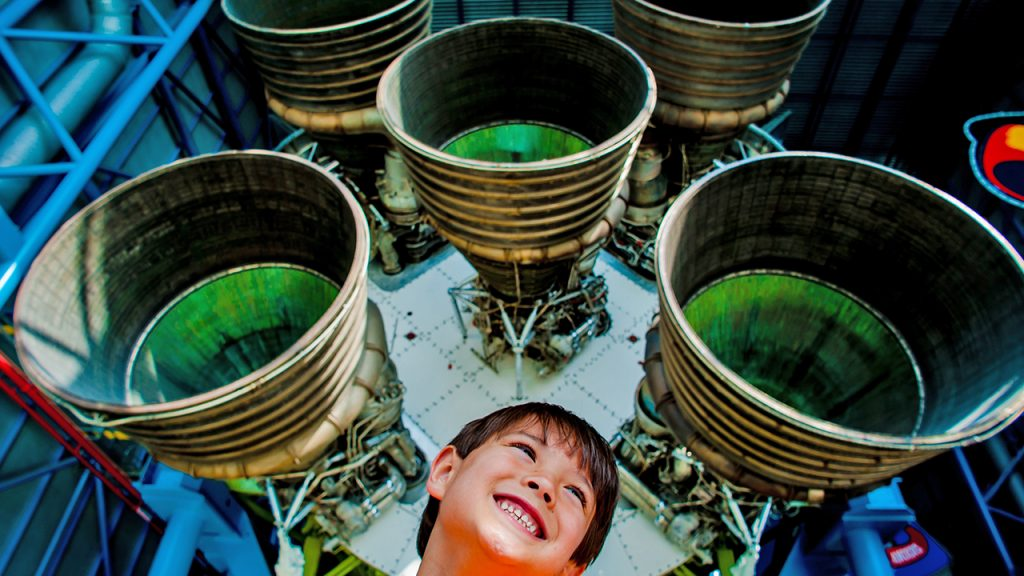 kid smiling under the jets of a rocket