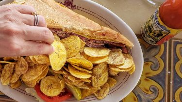 hand reaching in to eat plaintain chips of plate with Cuban sandwich