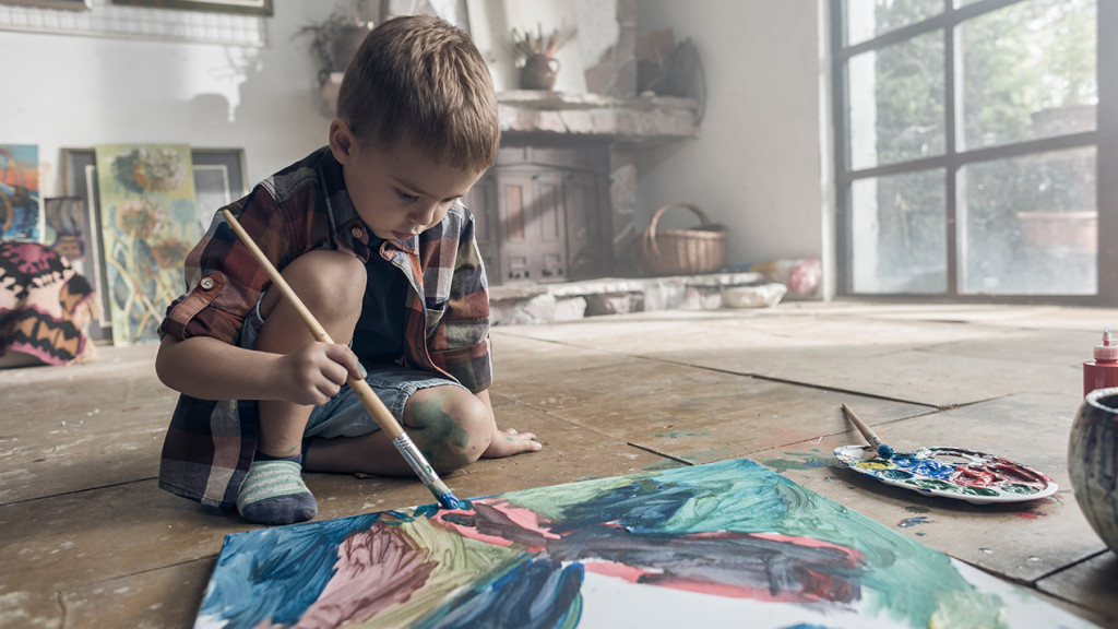 Young boy painting a canvas on the floor
