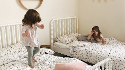 Siblings jumping on the beds in their shared room