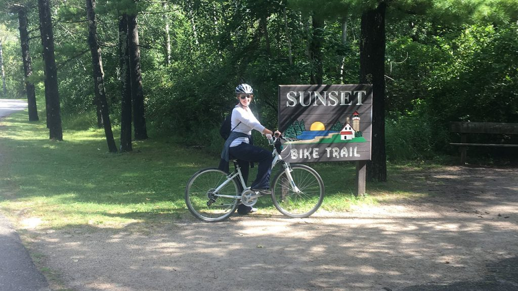 Woman on a bike in front of a biking trail sign things to do in door county