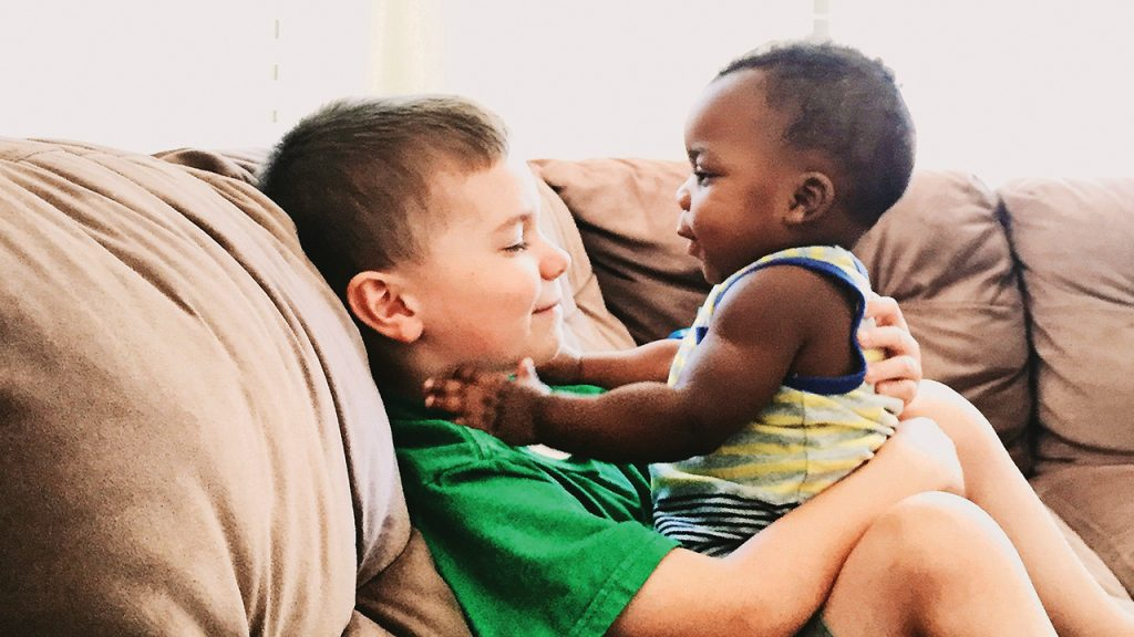 older sibling hold baby while sitting on the couch