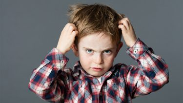 What does lice look like: Unhappy kid scratching his hair for head lice