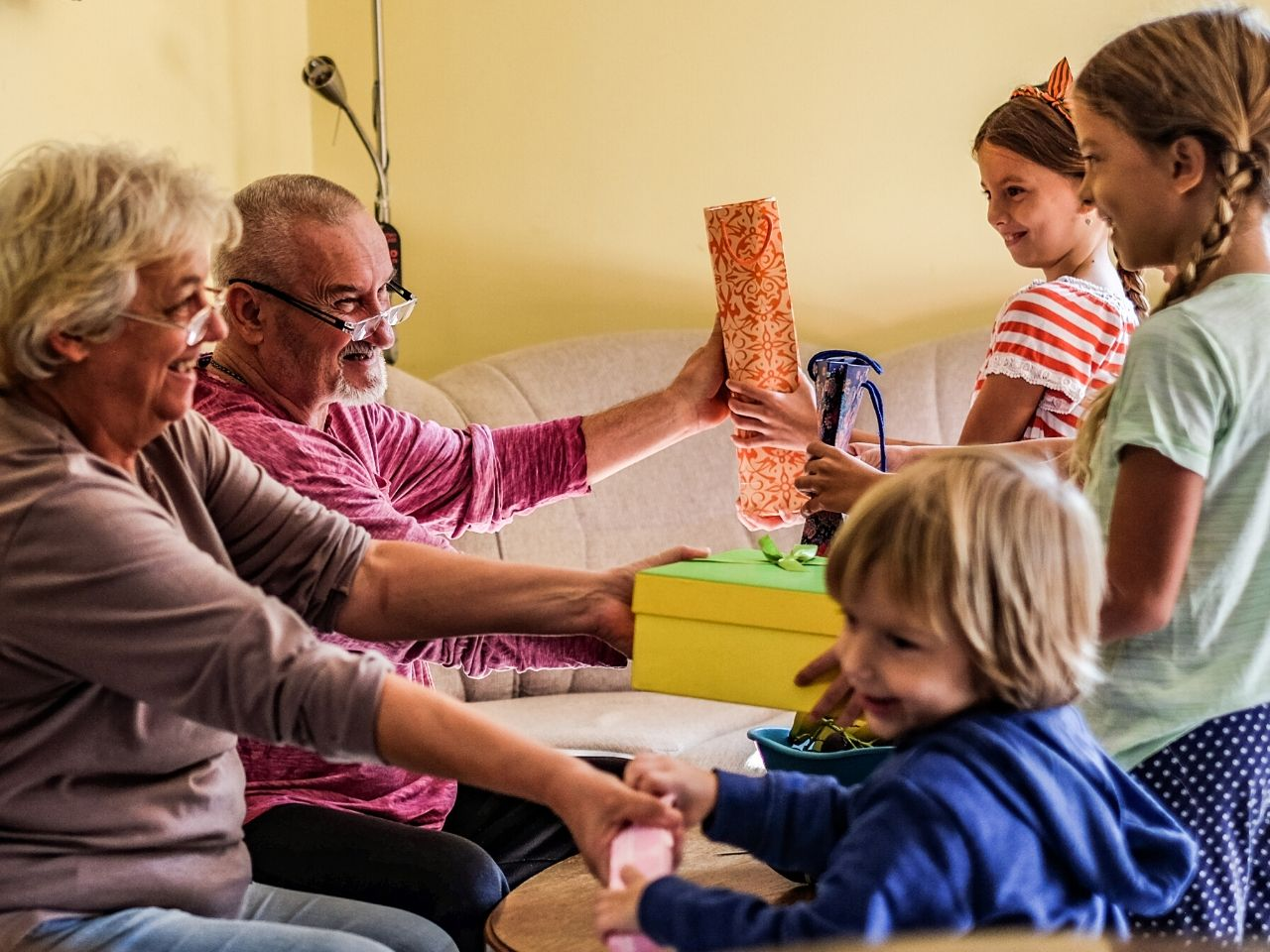 Grandparents give presents to three grandkids