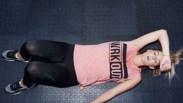 Kegel exercises: Women in workout clothes lays on floor looking tired