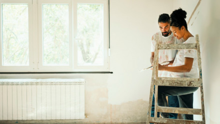 Nesting: Young couple renovating their home and painting a wall