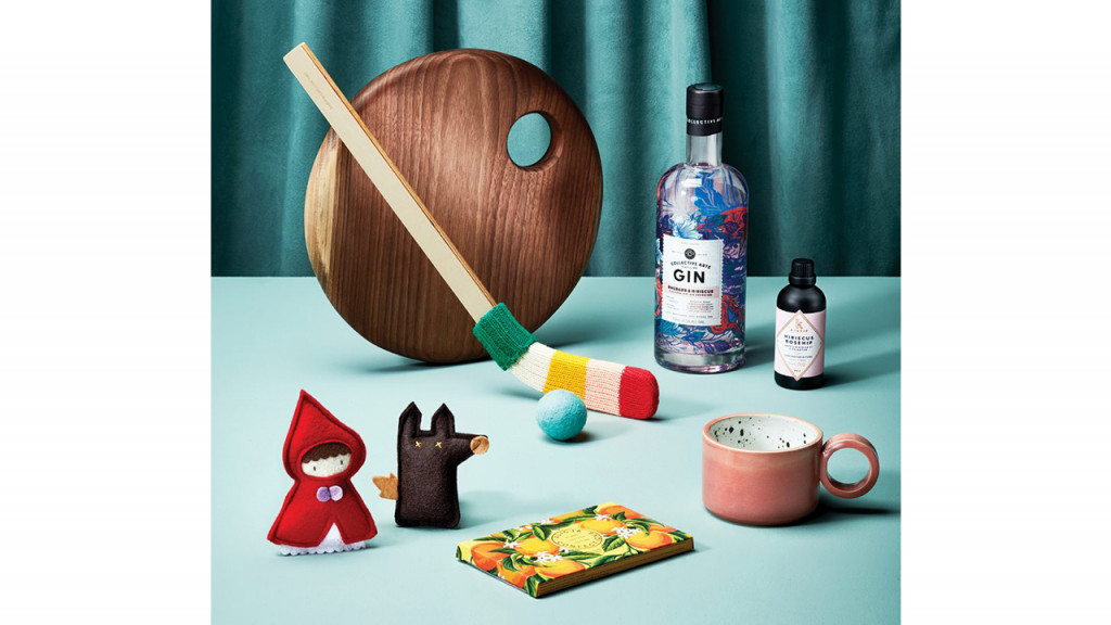 An assortment of gifts, including a bottle of gin, a wooden cheese board, a mini hockey stick, hand-made cat-nip filled cat toys, a ceramic mug, and a chocolate bar.