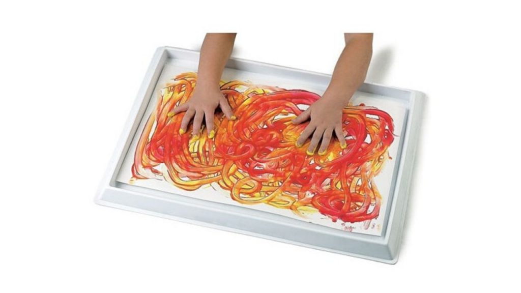 A child's hands spread red and yellow paint on the tray