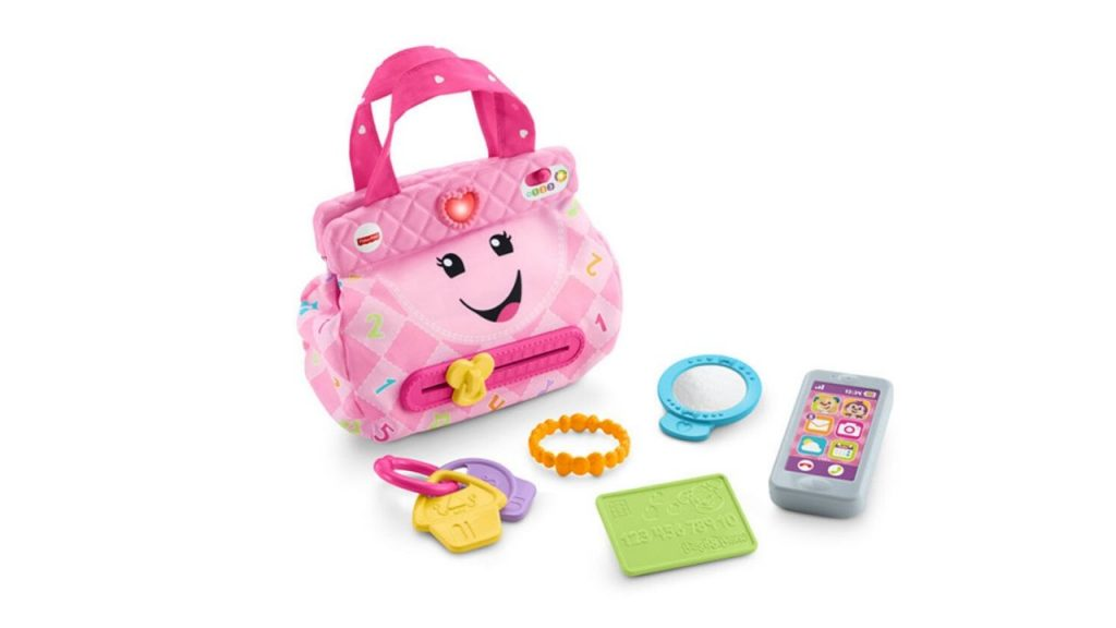 Pink purse with a smile on it surrounded by toy car keys, phone, mirror and bracelet