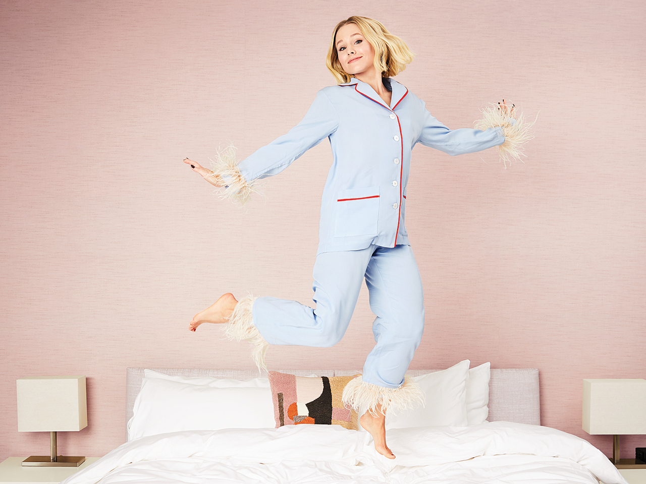 Kristen Bell jumping on a bed wearing pajamas with feathery cuffs