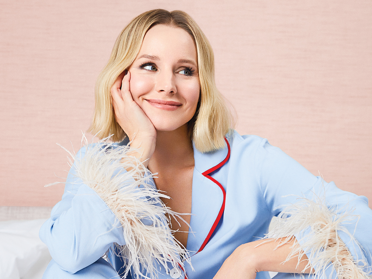Kristen Bell sitting on a bed leaning with her head on her hand wearing pajamas with feathery cuffs