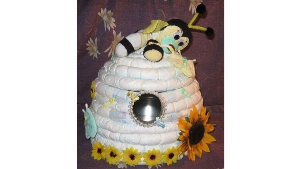 Diapers shaped into a beehive. Plush bee lays on top