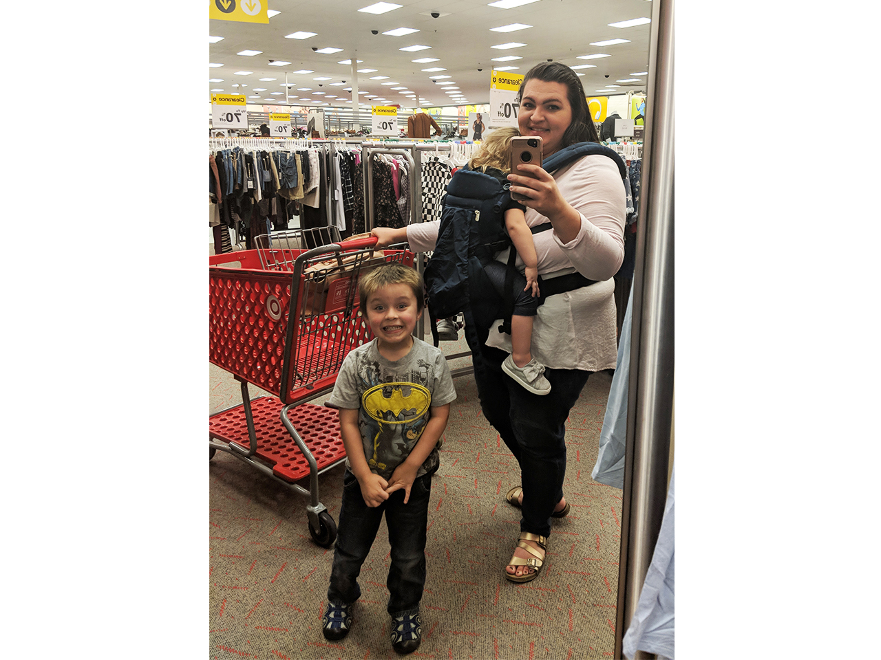 Mom in a store with her kids. one is sleeping in an Ergobaby Omni 360 baby carrier