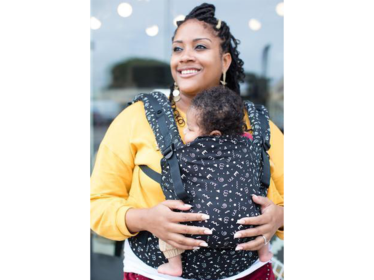 Mom carrying her baby in a Tula Free-to-Grow baby carrier