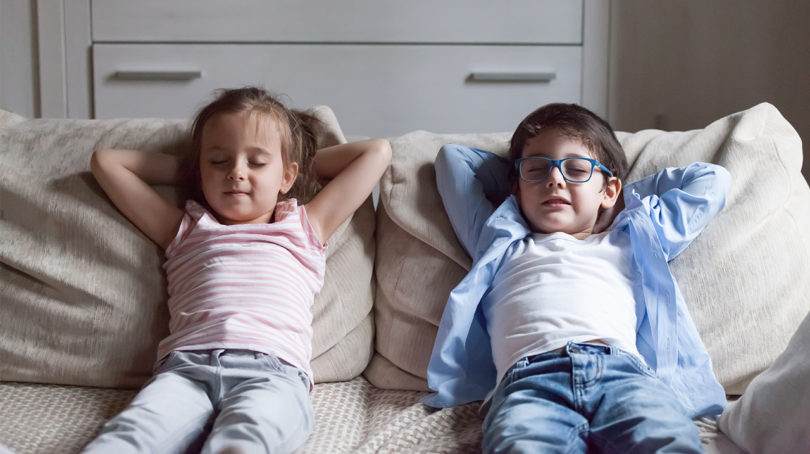 Siblings relax on couch with arms behind their head.