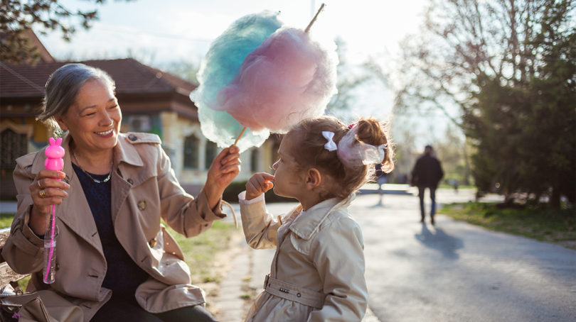 Grandma holds cotton candy and bubbles in her hands while granddaughter eats candy