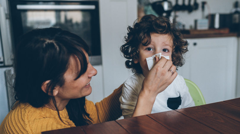 mom wiping kid's runny nose while they sit at the dining table