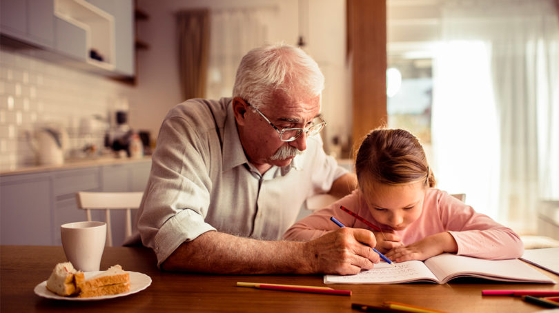 Grandpa with granddaughter colouring at the dining table.