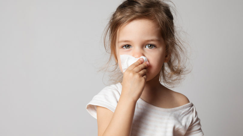little kid wiping their nose with a tissue