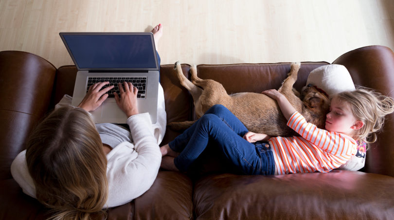 Mom working on laptop on couch with kid lying next to her
