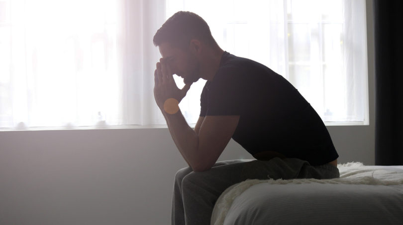 man looking upset while sitting on the edge of the bed