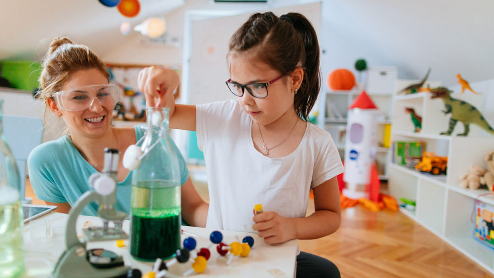 little kid doing science experiments at home with her mom