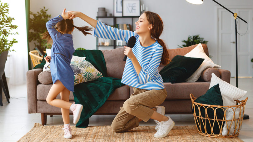 mom and girl singing into hairbrushes at home in the living room