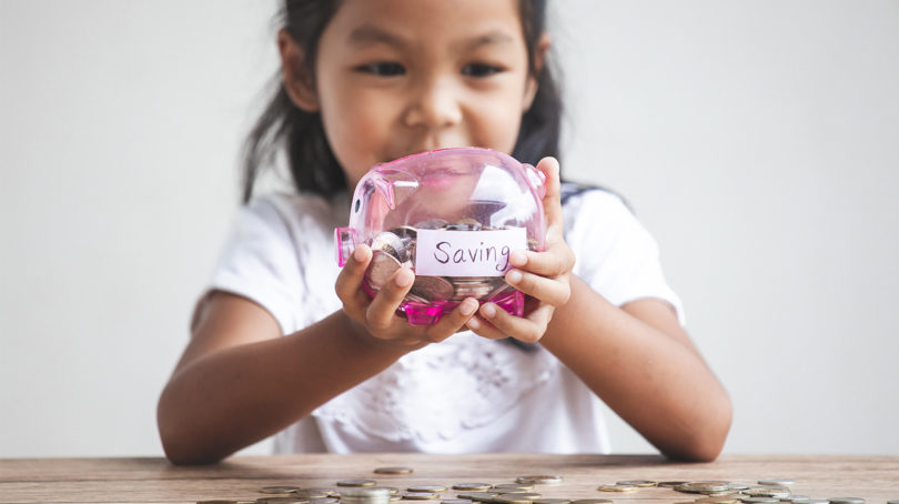 Girl holds piggy bank that holds her savings.