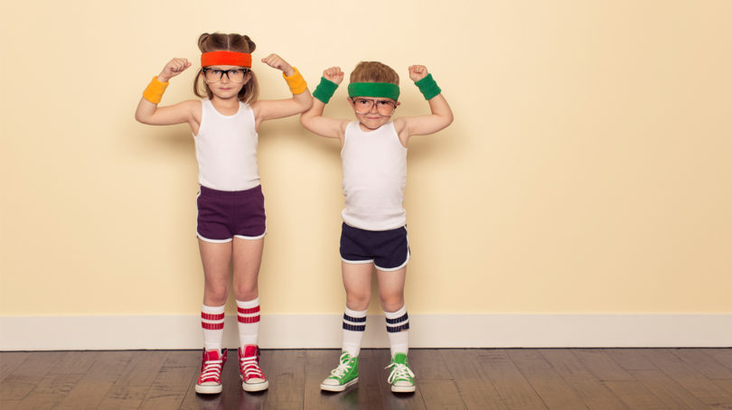 two kids posing inside while wearing athletic wear and sweatbands