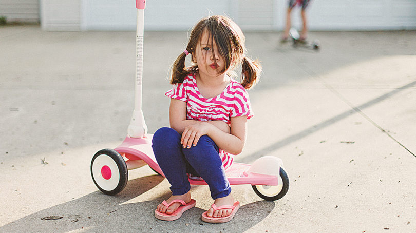 Little kid sits on a three wheel scooter looking sad