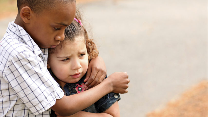 A little kid comforting a friend who's upset