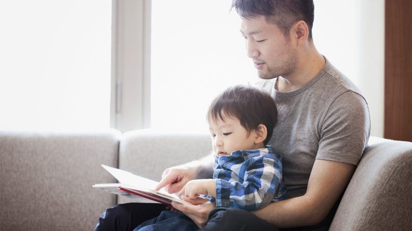 dad reading to his kid on the couch